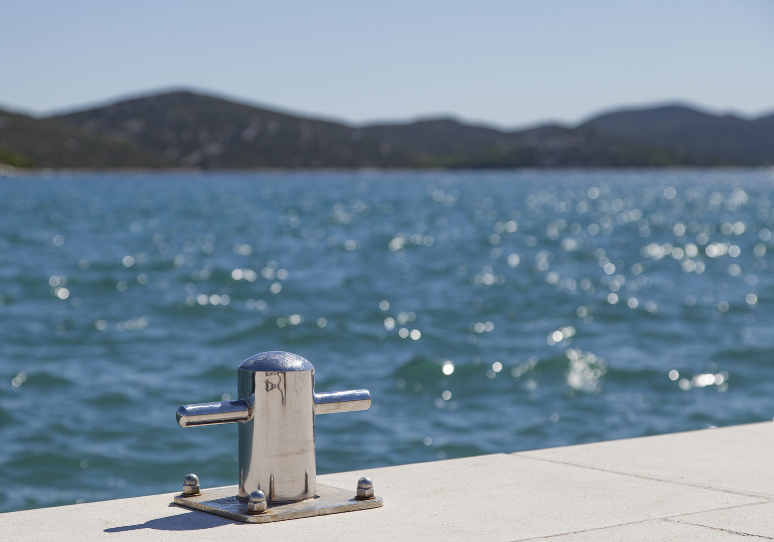 Metal mooring bollard on the dock of concrete harbor pier, selective focus on bollard, space for text