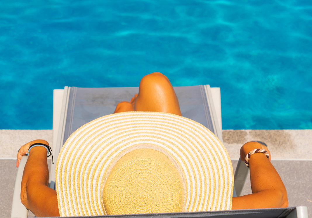 Woman relaxing on a sunbed at the swimming pool at the luxury tropical resort